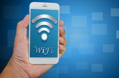 有WiFi象的手举行巧妙的电话 库存图片