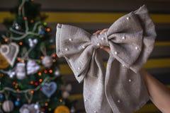 有xmas手工制造麻袋布弓的手 免版税库存照片