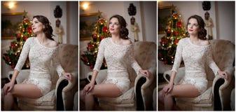 有Xmas树的美丽的性感的妇女在背景中坐在舒适风景的典雅的椅子 相当摆在女孩的画象  免版税库存照片