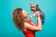 有yorkie狗的女孩 红色礼服的秀丽女孩拥抱在绿色背景隔绝的她的甜点约克夏狗 免版税库存图片