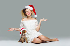 有yorkie狗的美丽的女孩在圣诞老人盖帽 库存图片