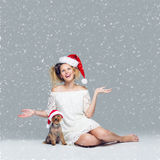 有yorkie狗的美丽的女孩在圣诞老人盖帽 免版税库存图片