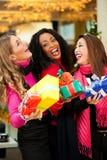 朋友与存在的圣诞节购物在购物中心 免版税库存照片