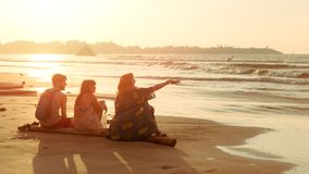 朋友两个少妇和人坐热带海边海滩在日落并且看水 夏天旅行,假期 库存图片