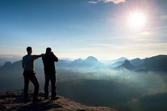 朋友二 远足者认为和照片热心者采取在峭壁的照片逗留 梦想的老保守风景,在好漂亮的东西或人的蓝色有薄雾的日出 免版税库存照片