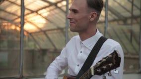 朋友享用一起弹吉他和唱歌在日落的年轻行家小组 股票视频