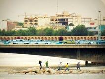 朋友享用伊斯法罕河沿在城市地平线和桥梁下 免版税库存图片