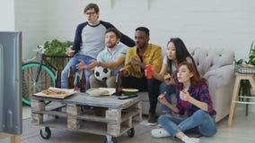 朋友体育迷观看在电视的橄榄球冠军一起吃薄饼和喝啤酒的不同种族的小组 股票视频