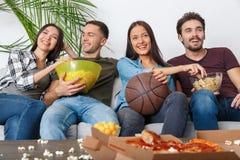 朋友体育迷观看篮球比赛吃快餐的小组 库存图片