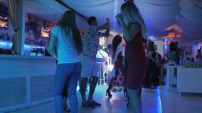 朋友公司跳舞在夜党、小组跳舞人靠近在晚上事件的酒吧柜台,男人和妇女 股票视频
