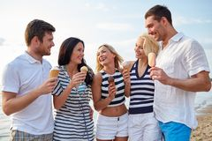 朋友吃冰淇凌和谈话在海滩 图库摄影