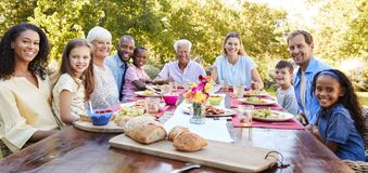 朋友和家庭吃午餐在庭院,看对照相机 免版税库存照片
