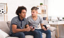 朋友和电子游戏 使用在控制台的两个少年游戏玩家 库存图片