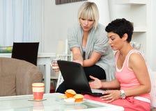 朋友回家膝上型计算机二妇女 免版税库存照片