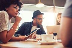 年轻朋友在与膝上型计算机和数字式片剂的一家咖啡店 库存图片