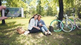 朋友在公园拍摄两个俏丽的女孩坐草坪使用拿着它的电话手中,在智能手机的焦点 股票视频