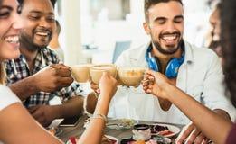 朋友在咖啡馆餐馆-人们t编组饮用的拿铁 库存图片
