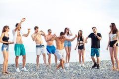 朋友在海滩跳舞在日落阳光下,获得乐趣,愉快,享用 图库摄影