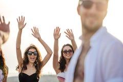 朋友在海滩跳舞在日落阳光下,获得乐趣,愉快,享用 免版税图库摄影