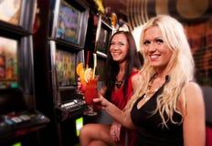 朋友在老虎机的赌博娱乐场 免版税库存照片
