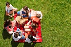朋友在野餐篮子附近坐绿色草甸 免版税图库摄影