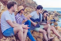 朋友坐在海滩的石头 人弹吉他 免版税库存照片