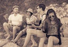 朋友坐在海滩的石头 人弹吉他 图库摄影