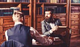 朋友坐扶手椅子在图书馆,葡萄酒样式里 免版税库存照片