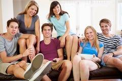 朋友坐沙发一起看电视的小组 库存图片