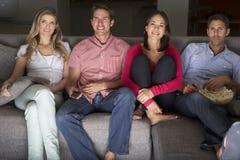 朋友坐沙发一起看电视的小组 免版税库存照片
