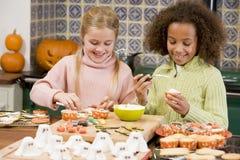 朋友女孩万圣节厨房二年轻人 免版税库存照片