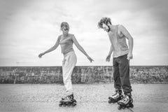 朋友学会一起rollerblading获得乐趣在公园 免版税库存图片