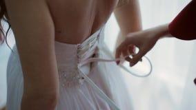 朋友帮助的新娘系带白色束腰样式成了串珠状婚礼礼服 股票视频