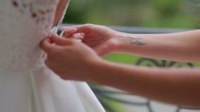 朋友帮助穿婚礼礼服的新娘 股票录像