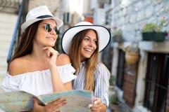 朋友微笑的gorup有地图的 旅游业、旅行、休闲、假日和友谊概念 库存图片