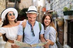 朋友微笑的gorup有地图的 旅游业、旅行、休闲、假日和友谊概念 免版税库存图片