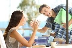 朋友或夫妇问候在咖啡店 免版税图库摄影