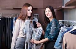 朋友执行购物并且讨论礼服 免版税库存图片