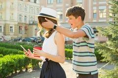 朋友是少年 男孩在会议上闭上了女孩` s眼睛用他的手,做惊奇 库存图片