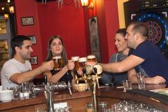 朋友有饮料在酒吧 免版税库存照片