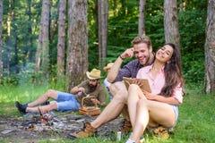 朋友松弛近的营火在会集的天以后远足或采蘑菇 暑假森林公司朋友夫妇 免版税图库摄影