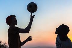 朋友现出轮廓的转动的橄榄球 免版税库存照片