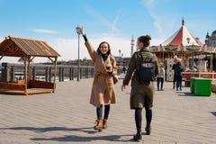 朋友的愉快的两个女学生在时髦的外套和背包的城市附近走并且喝从一次性杯子的咖啡, a 免版税库存图片