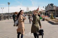 朋友的愉快的两个女学生在时髦的外套和背包的城市附近走并且喝从一次性杯子的咖啡, 图库摄影
