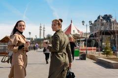 朋友的愉快的两个女学生在时髦的外套和背包的城市附近走并且喝从一次性杯子的咖啡, 免版税库存照片