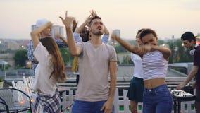 朋友站立与哀伤的面孔然后享受屋顶党、跳舞和微笑的感觉的小组的突然的心情变动 影视素材