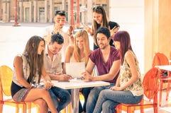 朋友编组坐在获得餐馆的酒吧与片剂p的乐趣 免版税库存图片