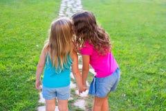 朋友耳语姐妹的女孩在耳朵的秘密 免版税库存照片