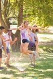 年轻朋友获得与水管的乐趣在公园 免版税库存图片