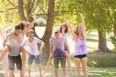 年轻朋友获得与水管的乐趣在公园 免版税库存照片